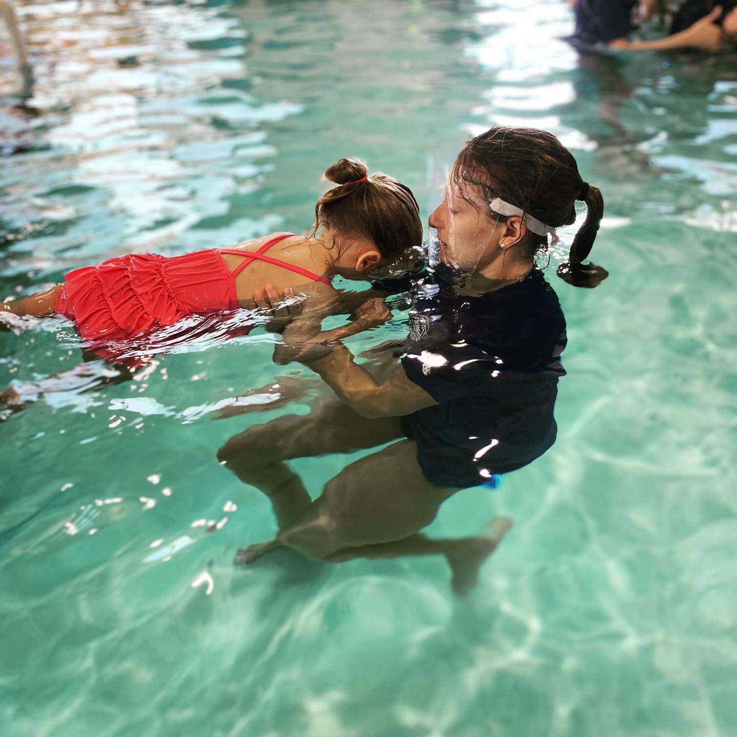 ASA Swim Instructor with face shield working with child face down in water
