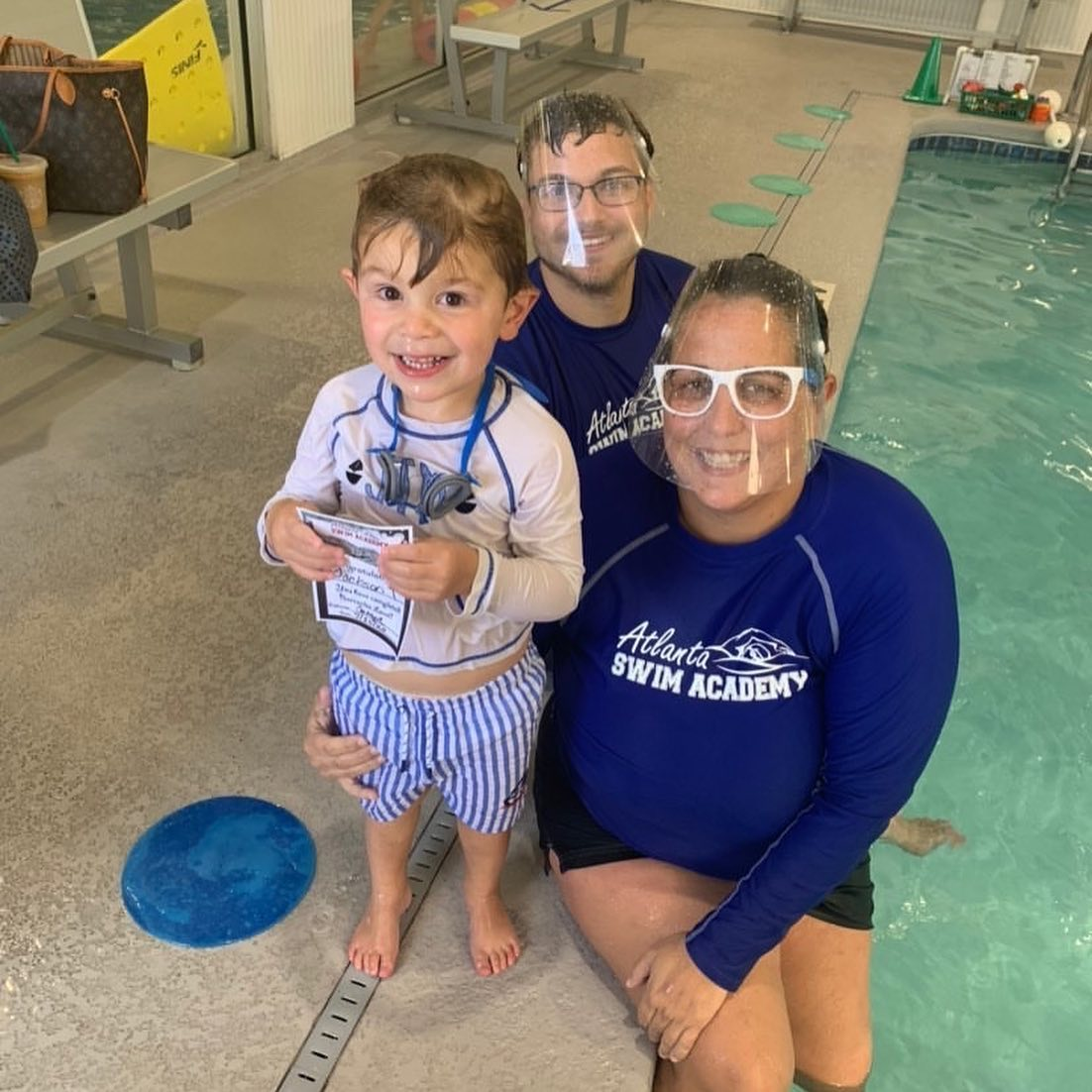 Swim Instructors with face shields sitting on edge of pool with student